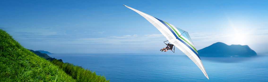 Man flying hangglider on the coast